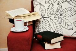 Stay at home auf Sofa mit Buch und Kaffee